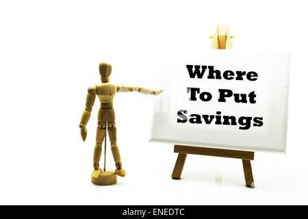 Wooden man with white board pointing at words 'where to put savings' save for future pension old age investment - Stock Photo