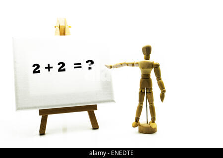 Wooden man with white board pointing at words '2 + 2 = ?' sum sums education educational concept math maths arithmetic - Stock Photo