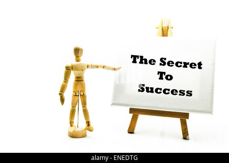 Wooden man with white board pointing at words 'the secret to success' secrets hidden truths hard work - Stock Photo