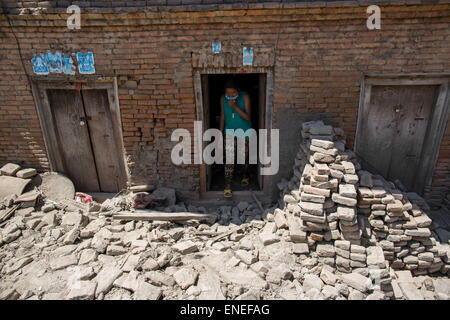 Kathmandu, Nepal. 3rd May, 2015. A woman is leaving from her damaged house where rubbles are everywhere around in - Stock Photo