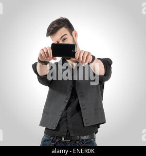Young bearded man taking photo with his smart phone camera. Desaturated over retro vignette studio background - Stock Photo