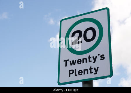 Twenty's plenty road sign against blue sky with white clouds on a sunny day - Stock Photo