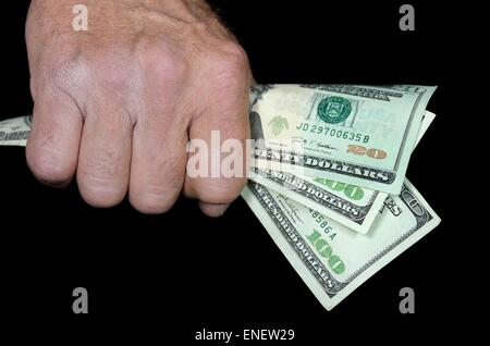 Man holding a American currency in his fist. - Stock Photo