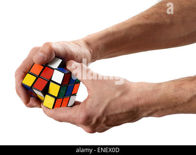 Man twisting a Rubik's cube puzzle with scrambled colors - Stock Photo