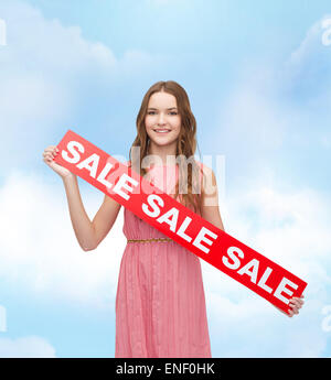 young woman in dress with sale sign - Stock Photo