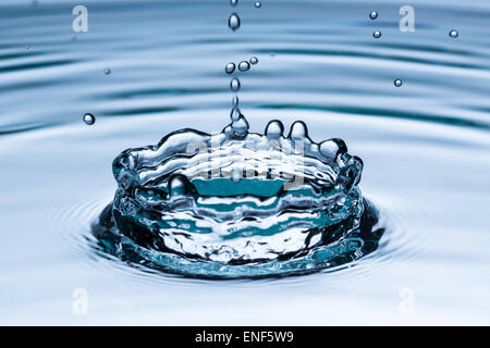Drop of water falling into water surface, macro photo - Stock Photo