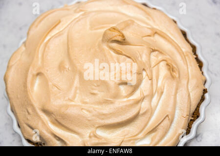 Fresh, delicious home cooked lemon meringue pie in a round white scalloped pie dish - Stock Photo