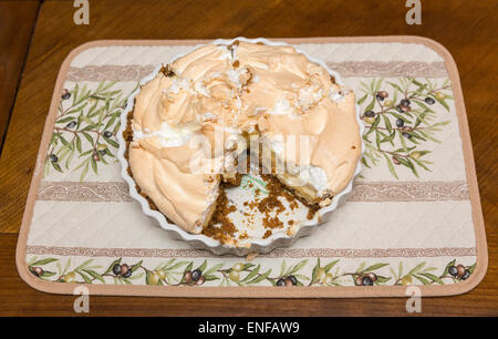 Fresh, delicious home cooked lemon meringue pie in its dish with a slice taken out - Stock Photo