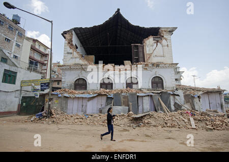 Kathmandu, Nepal. 25th Apr, 2015. A girl walks by the heavily damaged south section of Durbar High School located - Stock Photo