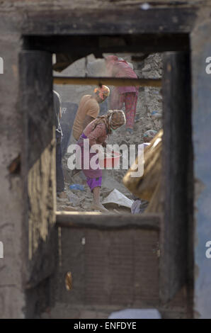 Bhaktapur, Nepal. 25th Apr, 2015. A woman cleaning the debris of her house to collect her belongings after the house - Stock Photo