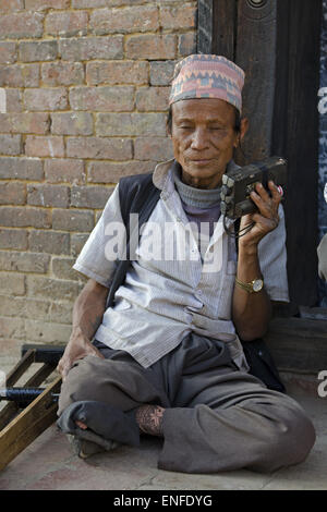 Bhaktapur, Nepal. 25th Apr, 2015. An old man listens to the news of the earthquake on a portable radio as electricity - Stock Photo