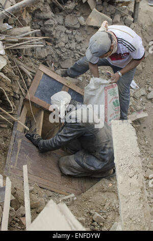Bhaktapur, Nepal. 25th Apr, 2015. A man recovering his belongings from a wooden shelf which was buried under the - Stock Photo