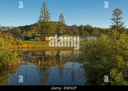 Waterfront holiday resort accommodation with blue sky and trees reflected in calm water of lake at Nambucca Heads - Stock Photo