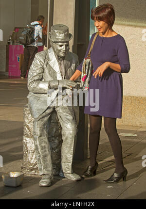Man busking as living statue with silver body, clothes and hat interacting with smiling Asian woman at Circular - Stock Photo