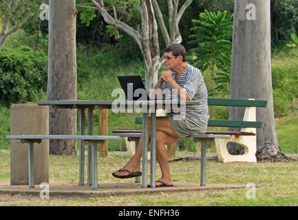 Man seated at picnic table in public park using laptop computer - background of trees and emerald green vegetation - Stock Photo