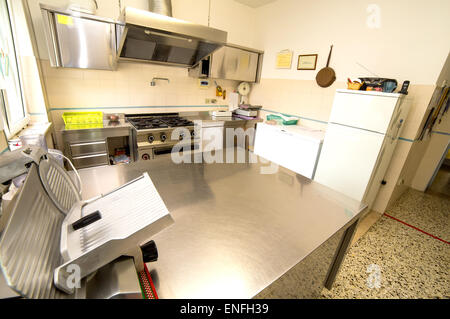 huge stainless steel kitchen with gas stove and a meat slicer - Stock Photo