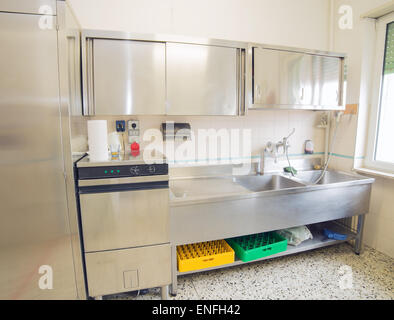 large industrial kitchen with refrigerator, dishwasher and sink all stainless steel - Stock Photo