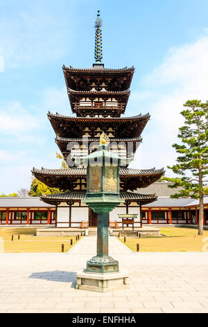 Japan, Nara, Yakushiji temple. Unrestored West pagoda, dating back to the Hakuho period. Bronze lantern in foreground. - Stock Photo