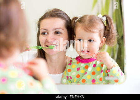 mother teaching daughter child teeth brushing in bathroom - Stock Photo