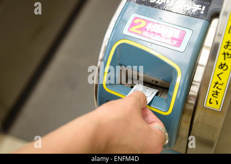 Hand inserting train ticket into ticket gate/turnstile in Japan. Japanese automation. - Stock Photo