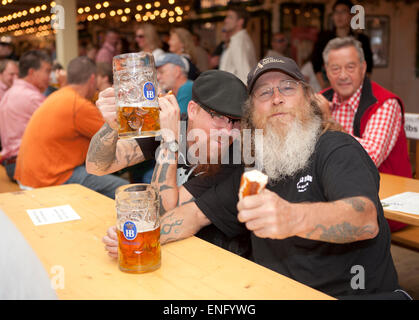 Visitors sit in the beer tent at the Oktoberfest with a beer mug - Stock Photo