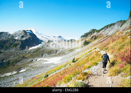 Woman hiking on rocky trail on remote hillside - Stock Photo