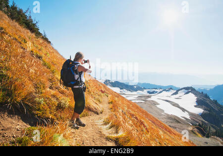 Woman taking photograph of remote mountains on hillside - Stock Photo