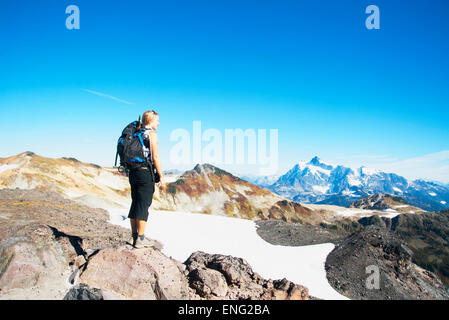 Woman admiring mountains in remote landscape - Stock Photo
