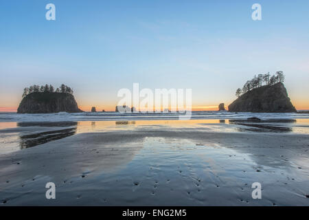 Sunrise horizon behind rock formations on beach - Stock Photo