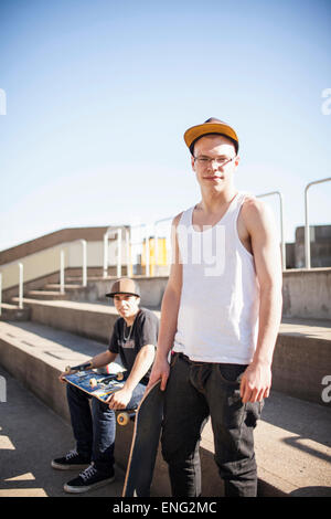 Caucasian men with skateboards sitting on steps - Stock Photo