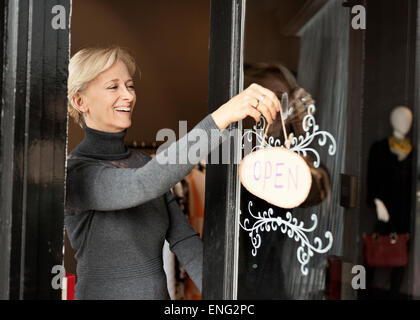 Caucasian small business owner hanging open sign on front door - Stock Photo