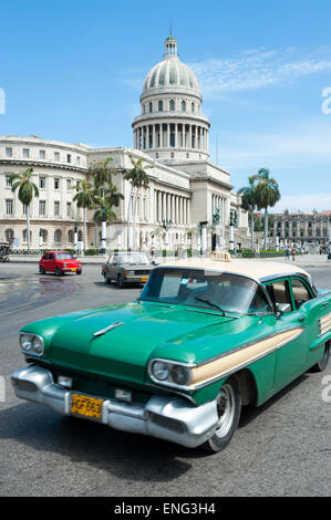 HAVANA, CUBA - JUNE, 2011: Classic American Cuban taxi car passes in front of the Capitolio building in Central - Stock Photo
