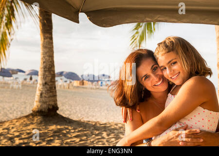 Mother and daughter hugging under umbrella on beach