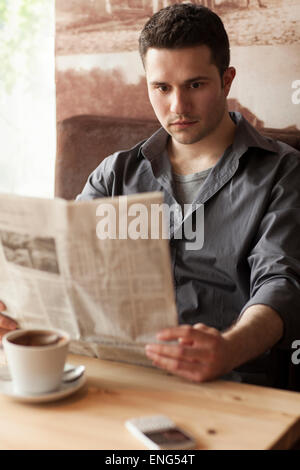 Man reading newspaper and drinking coffee in cafe