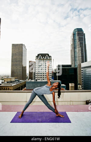 African American woman practicing yoga on urban rooftop - Stock Photo