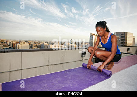 African American woman rolling yoga mat on urban rooftop - Stock Photo