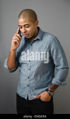 Mixed race man talking on cell phone - Stock Photo