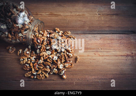 Walnut kernels and whole walnuts on rustic old wooden table glass jar - Stock Photo