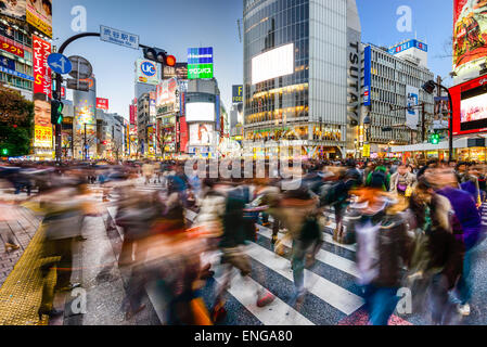 Pedestrians walk at Shibuya Crossing during the holiday season. The scramble crosswalk is one of the largest in - Stock Photo