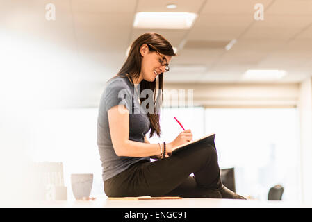 A young woman seated on her desk writing in a notebook with a red pen. - Stock Photo