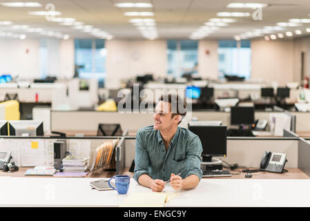 A young man seated at a desk in an office. - Stock Photo