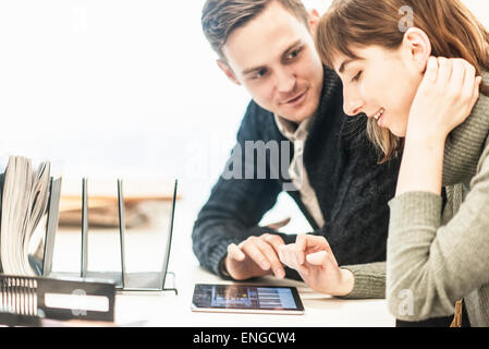 A man and a woman seated side by side talking at a desk in an office. - Stock Photo