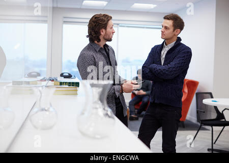 Two men in an office, standing and talking, one with his arms folded. - Stock Photo