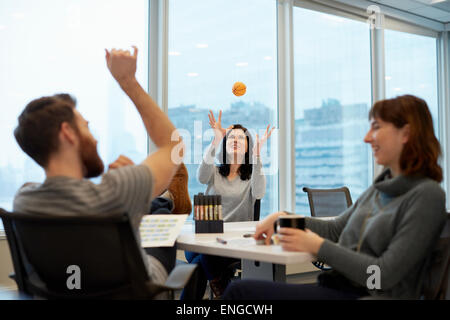 Three business people, two women and a man, reaching up to catch a ball. - Stock Photo