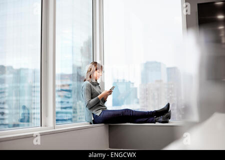 A woman holding a smart phone, sitting on a window ledge. - Stock Photo