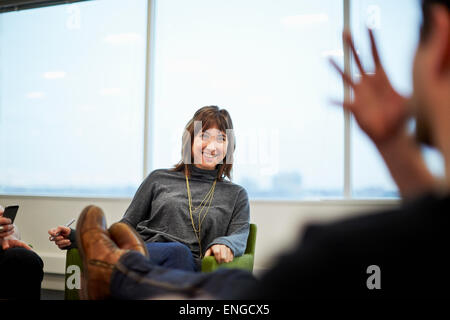 A woman seated in an office talking to someone with their feet up on the table. - Stock Photo