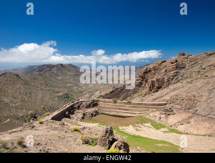 Gran Canaria, Barranco de Soria, empty water reservoir on the wall of the valley - Stock Photo