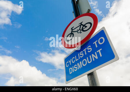 Sign warning cyclists to dismount before proceeding. - Stock Photo