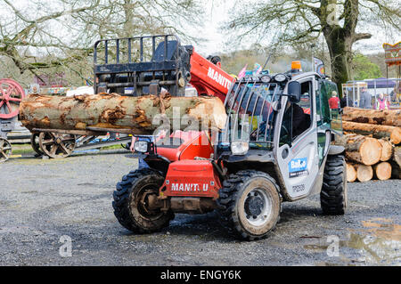 A Manitou forklift truck lifts a tree trunk at a sawmill. - Stock Photo