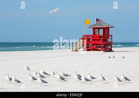 Red wooden lifeguard hut on an empty beach - Stock Photo